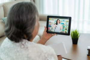 senior citizen woman looking at tablet screen for telehealth visit