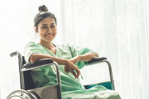 happy patient sitting in wheelchair in hospital telehealth